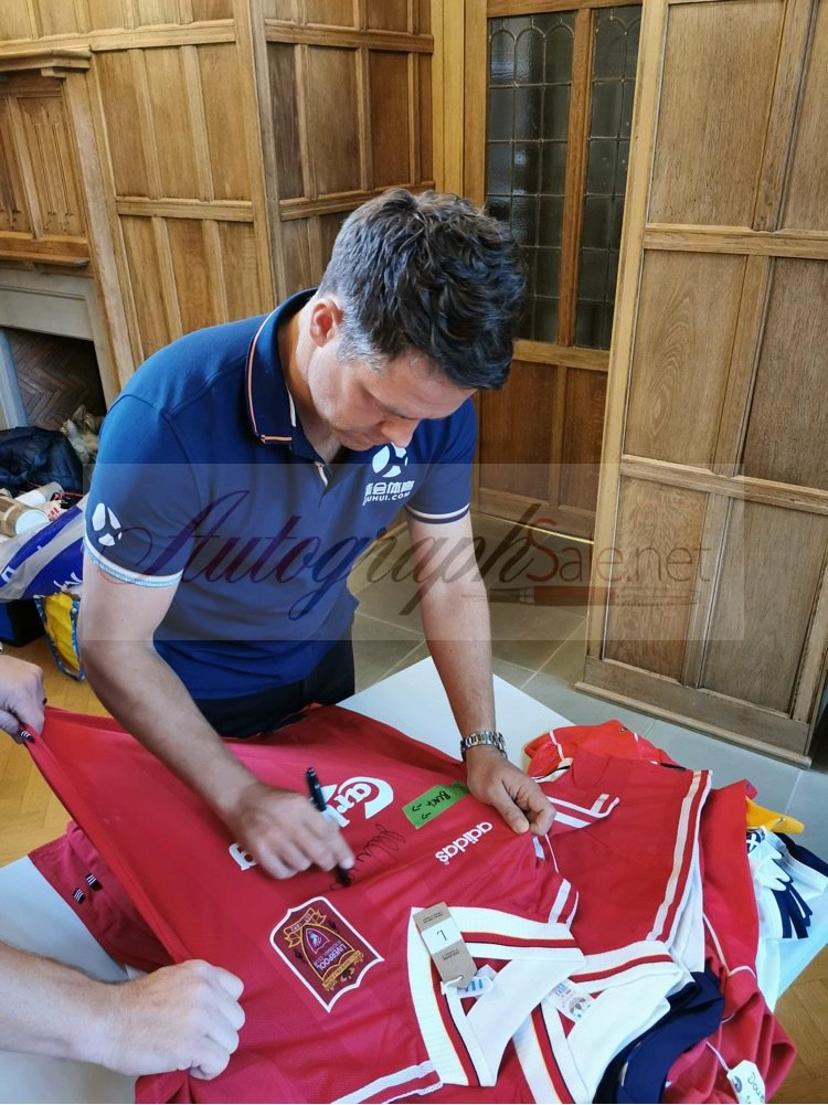 Liverpool shirts being signed by Michael Owen